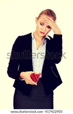 Shocked business woman looking into her empty wallet - stock photo