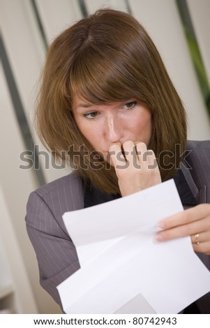 shocked business woman reading a letter with bad news