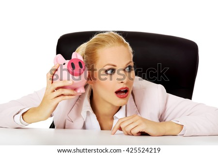 Shocked business woman sitting behind the desk and listen too her piggybank - stock photo