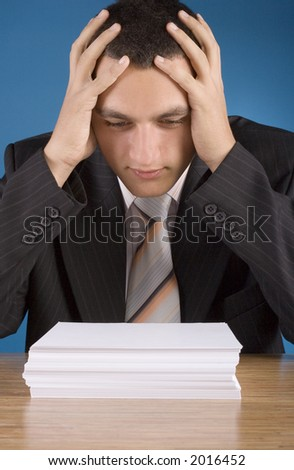 shocked businessman at the  stack of documents (blue background) - stock photo