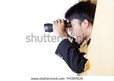 Shocked businessman breaking through a paper wall looking through binoculars