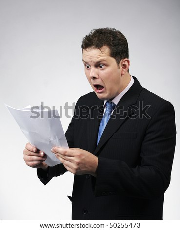 Shocked businessman looking at documents. Studio shots. - stock photo