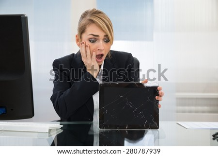 Shocked Businesswoman Holding Broken Screen Digital Tablet In Office - stock photo