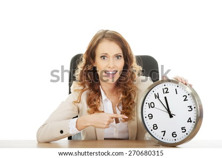Shocked businesswoman with clock by a desk.