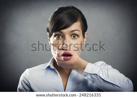 Shocked businesswoman with mouth open, isolated on grey background. - stock photo