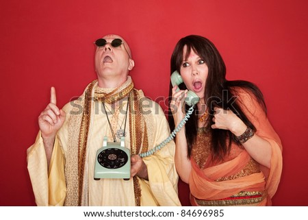 Shocked Caucasian on phone call while bald monk points index finger upward toward heaven - stock photo