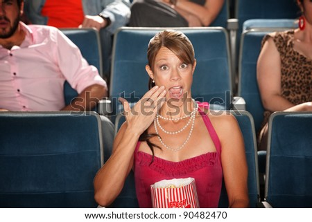 Shocked Caucasian woman watches movie with eyes and mouth wide open