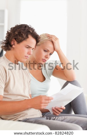 Shocked couple reading letters in the living room - stock photo