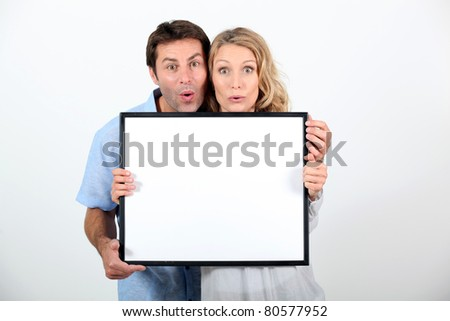 Shocked couple stood with blank message board - stock photo