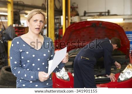 Shocked Customer Looking At Garage Bill - stock photo