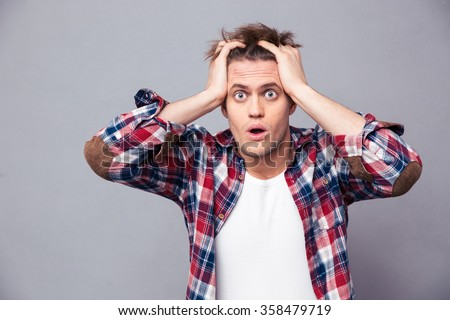 Shocked dazed young man in plaid shirt holding head with both hands over grey background - stock photo