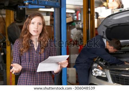 Shocked Female Customer Looking At Garage Bill - stock photo