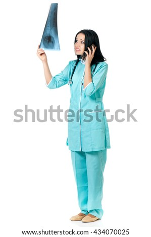 Shocked female doctor examining a patient's x-ray, she  talking on phone