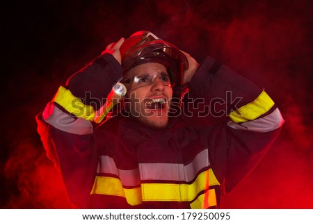 Shocked firefighter in action. Shouting fireman in smoke holding hands on helmet and looking up. Head and shoulders studio shot on black background. - stock photo