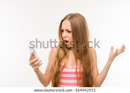 Shocked frustrated young woman with phone - stock photo