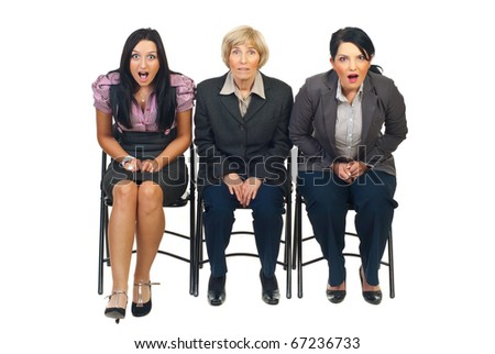 Shocked group of businesswomen sittingon chair at conference isolated on white background - stock photo