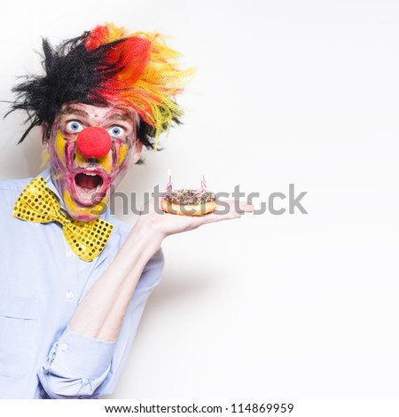 Shocked Happy Birthday Clown Holding Doughnut Party Cake With Two Candles During A Childs Birthday Party On Copy Space Background - stock photo