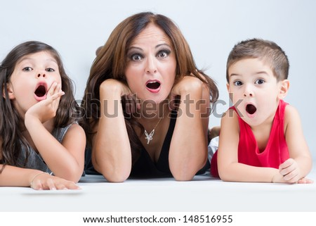 Shocked kids and their mom looking at camera - stock photo