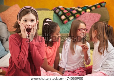 Shocked Little Caucasian girl with friends at a sleepover - stock photo