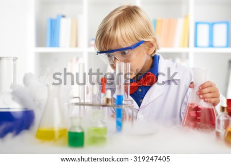 Shocked little chemist looking at smoke trailing on the table