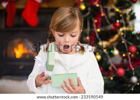 Shocked little girl opening a gift at home in the living room - stock photo
