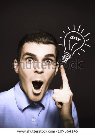 Shocked male business person pointing to light bulb illustration in a bright spark of ideas concept on dark copy space background - stock photo