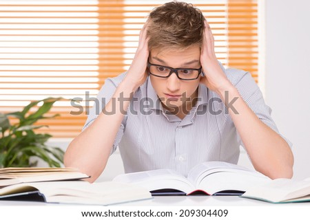 shocked male student working in studio. University student with many books at desk learning for exams  - stock photo