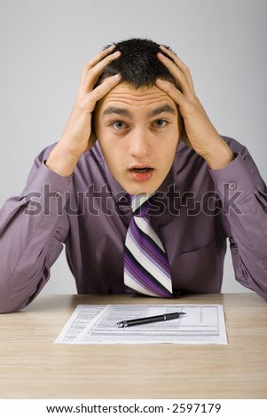 Shocked man at the desk. There's some papers on the desk and a pen. (paper's form is copyright free) - stock photo