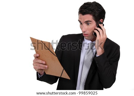 Shocked man looking at a file folder - stock photo