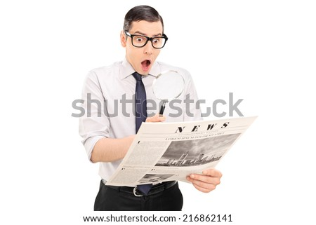 Shocked man reading the news through a magnifier isolated on white background - stock photo