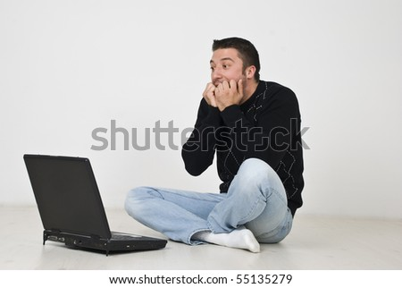 Shocked man sitting on floor in profile and biting his nails in front of laptop - stock photo