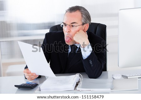 Shocked Mature Businessman Sticking Tongue Out While Holding Paper - stock photo