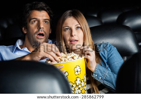 Shocked mid adult couple having popcorn while watching movie in cinema theater - stock photo