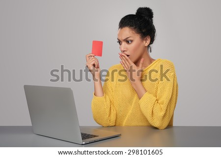 Shocked mixed race african american - caucasian woman with laptop computer holding blank credit card, sitting at table, over gray background - stock photo