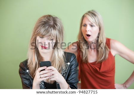 Shocked mom watches teen use phone over green background - stock photo
