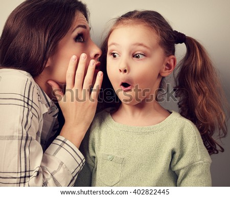 Shocked mother whispering the secret information to her surprising cute girl in ear on blue background - stock photo