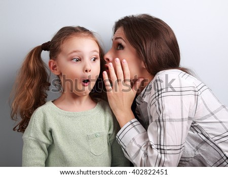 Shocked mother whispering the secret information to her surprising cute girl in ear on blue background