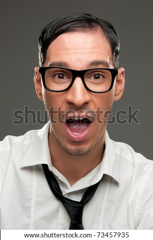 Shocked nerd with open mouth looking at camera - stock photo