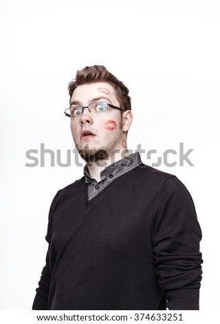 Shocked nerdy guy with footprints from red lipstick on his cheek. Concept of gratefulness girls. - stock photo