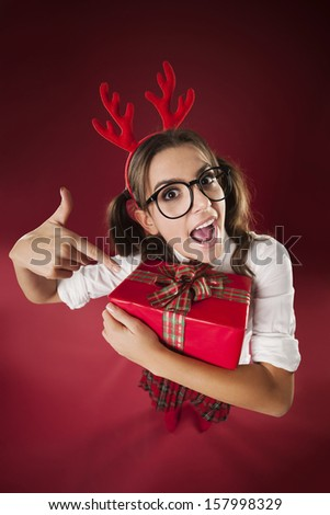 Shocked nerdy woman pointing at christmas gift  - stock photo