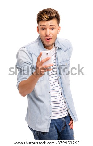 Shocked news! Studio portrait of amazed young man using smartphone. Isolated on white. - stock photo