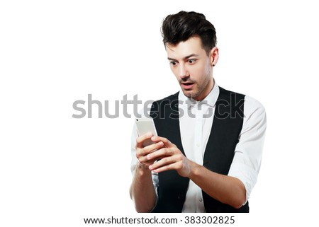 Shocked news! Studio portrait of amazed young man using smartphone. Isolated on white.