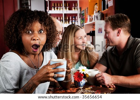 Shocked Pretty African American Woman in Coffee House with Friends