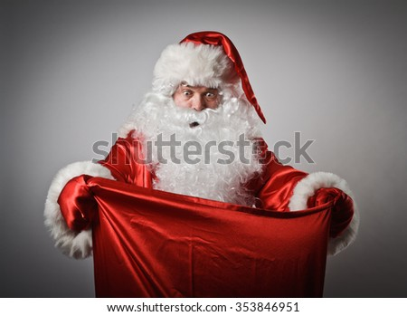 Shocked Santa Claus is looking in to the sack.