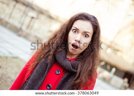Shocked scared crying pretty woman with brown eyes and hair in bright red coat and dark scarf standing on the street
