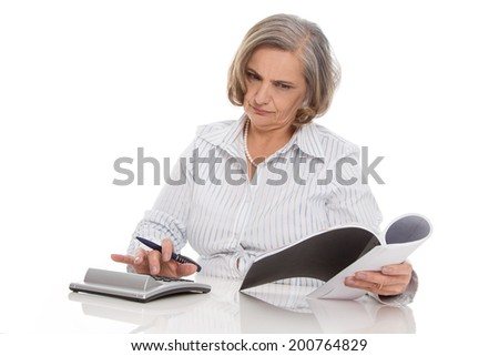 Shocked senior businesswoman looking at increasing costs. - stock photo