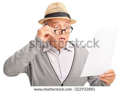 Shocked senior gentleman looking at the bills in disbelief isolated on white background - stock photo