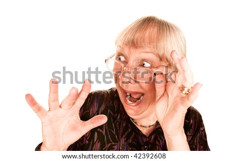 Shocked senior woman looking sideways over the top of her glasses - stock photo