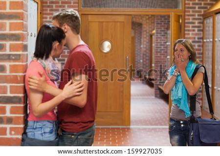 Shocked student finding her boyfriend cheating in school - stock photo
