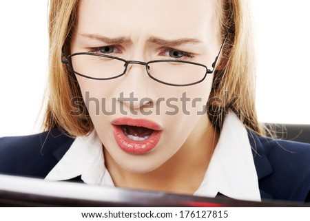 Shocked, surprised business woman sitting in front of laptop. Isolated on white. - stock photo
